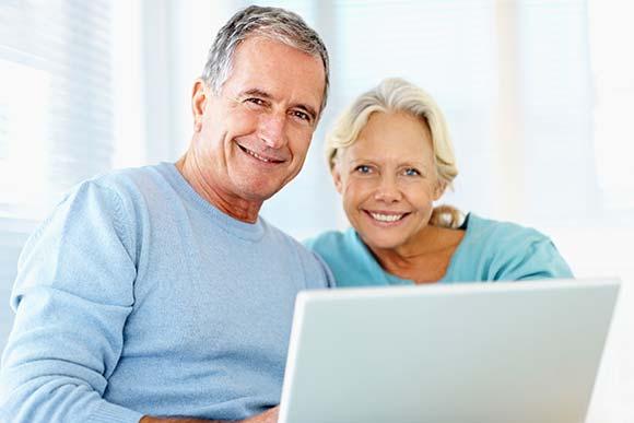 Älteres Paar informiert sich am Laptop über urologische Behandlungen.